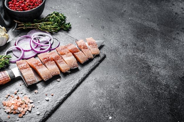 タマネギとピンクの塩で塩漬けオランダニシンのスライスしたフィレ。黒の背景。上面図。スペースをコピーします。