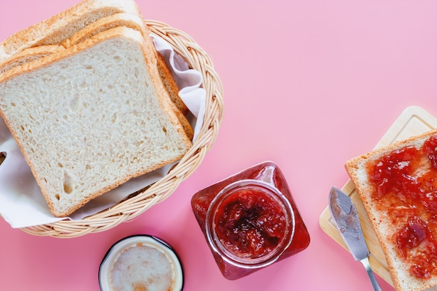 Sliced fine whole wheat bread with strawberry spread on pink background