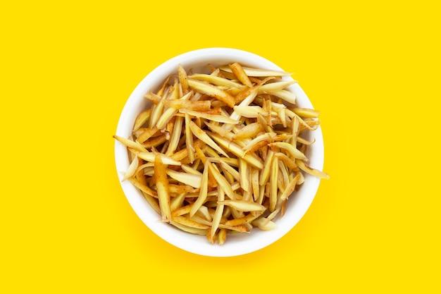 노란색 배경에 흰색 그릇에 얇게 썬 손가락 뿌리.