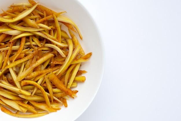 흰색 바탕에 흰색 접시에 얇게 썬 손가락 뿌리.