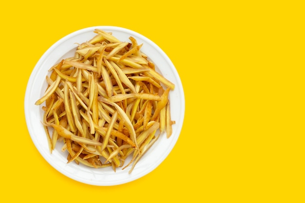 Sliced finger root in white plate on yellow background.