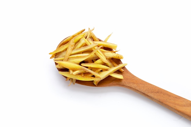 Sliced fingerroot in wooden spoon on white background.