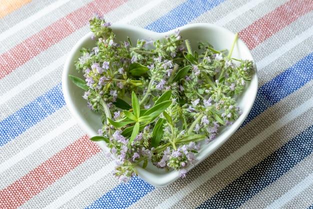 縞模様のテキスタイルテーブルクロスを背景に白いハート型のプレートにスライスされた開花タイム