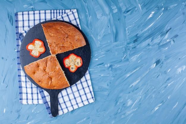 Нарезанный ароматный хлеб с дольками перца на черной разделочной доске.