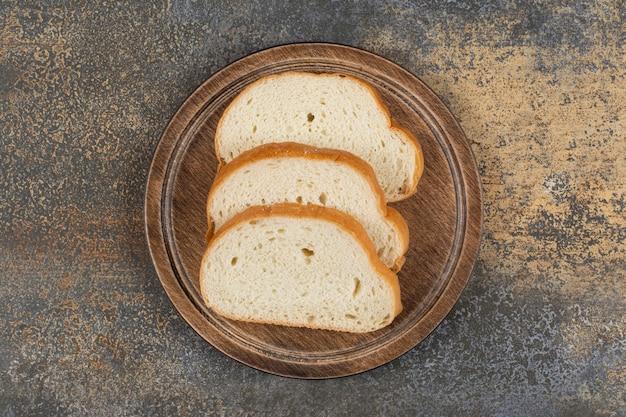 Sliced fragrant bread on wooden cutting board.