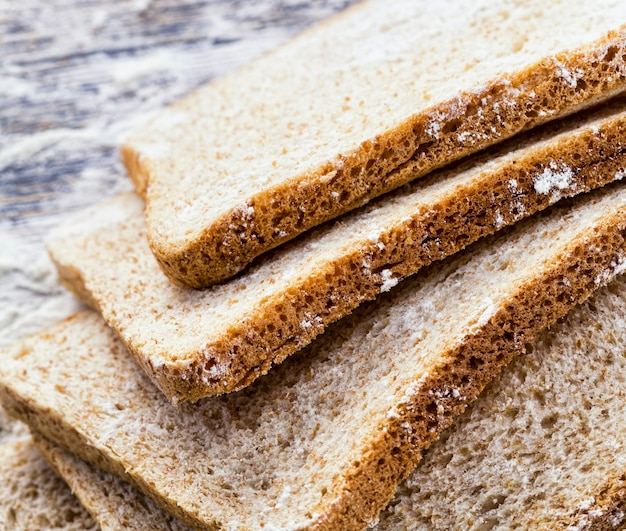 Нарезанный свежий хлеб в белой пшеничной муке, крупный план еды на столе