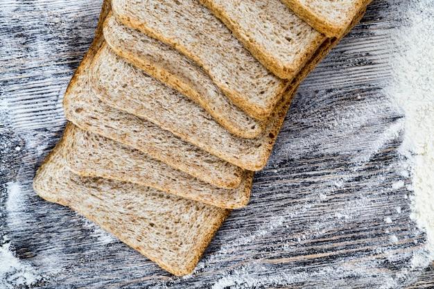 Нарезанный свежий хлеб в белой пшеничной муке, крупный план еды