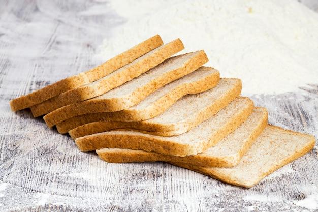 Нарезанный свежий хлеб в белой пшеничной муке, крупным планом еды на столе