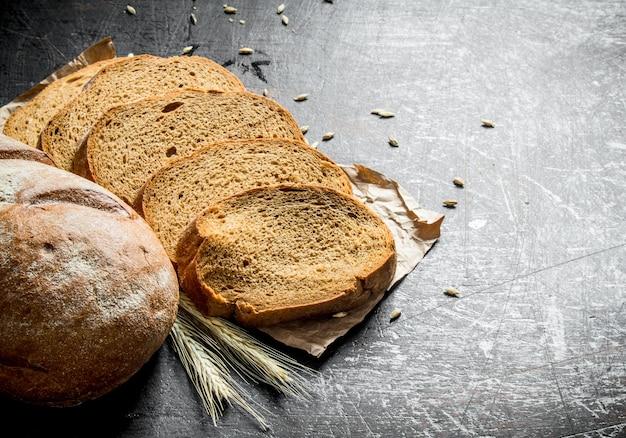 Нарезанный свежий хлеб. на темном деревенском фоне