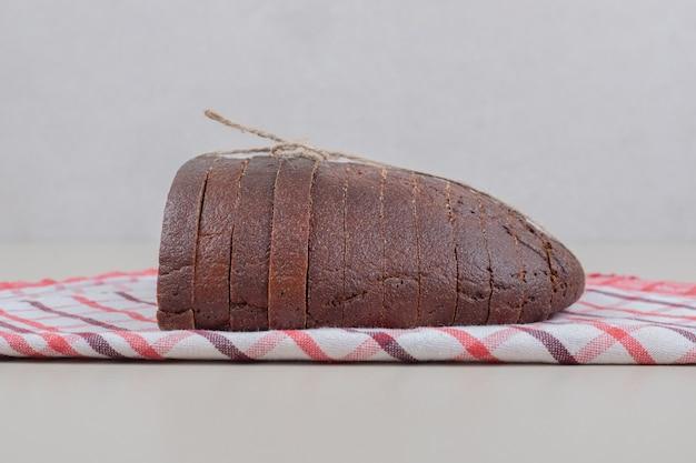 Нарезанный свежий черный хлеб в веревке на скатерти. фото высокого качества