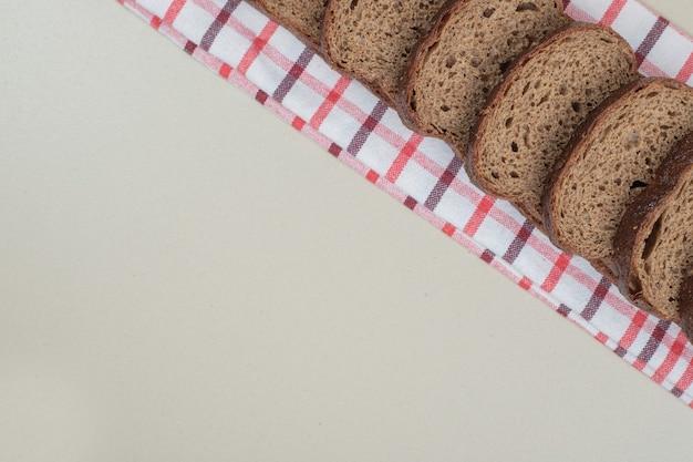 テーブルクロスに焼きたての茶色のパンをスライスしました。高品質の写真