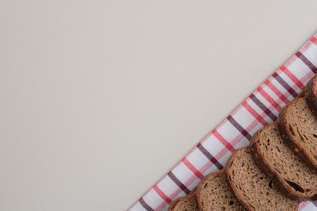 Нарезанный свежий черный хлеб на скатерти. фото высокого качества