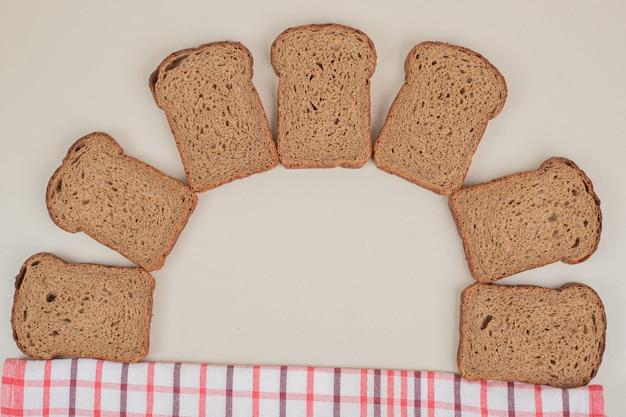 흰색 표면에 신선한 브라운 빵을 슬라이스