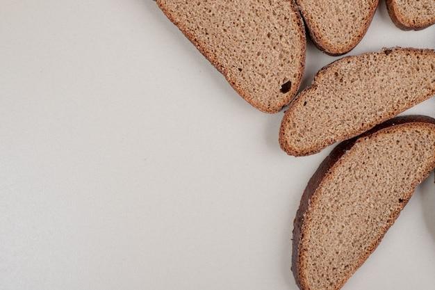 白い表面にスライスした焼きたての茶色のパン