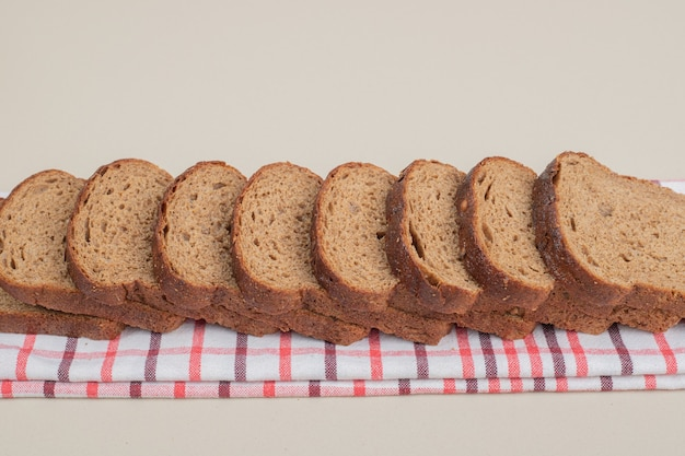 Pane integrale fresco affettato sulla tovaglia