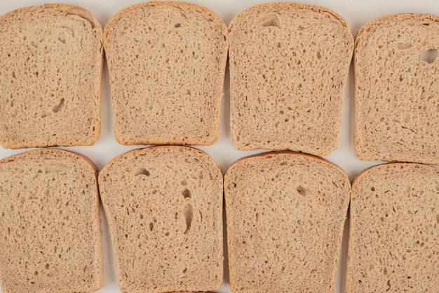Pane integrale fresco affettato sulla superficie bianca