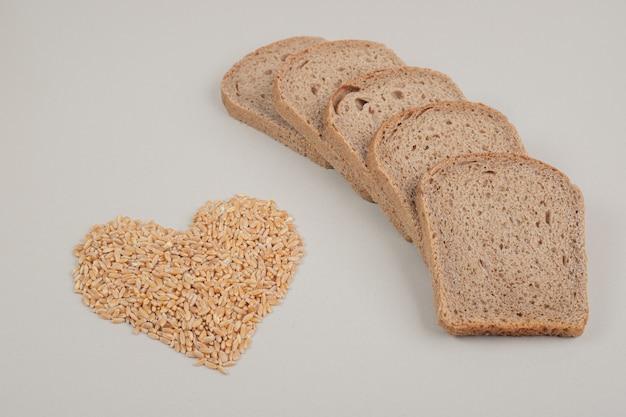 白い背景にオート麦の穀物とスライスした新鮮な茶色のパン。高品質の写真