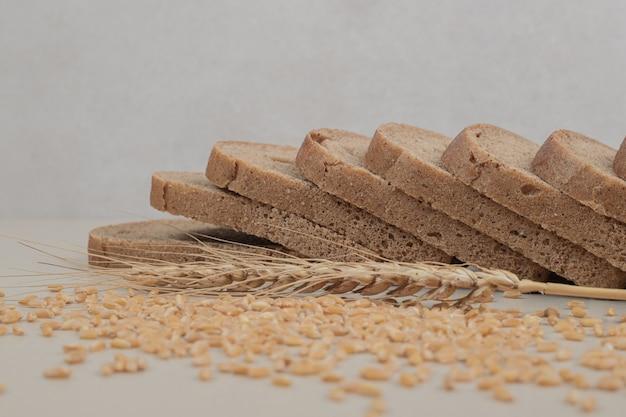 白い表面にオーツ麦の粒が付いたスライスした焼きたての茶色のパン