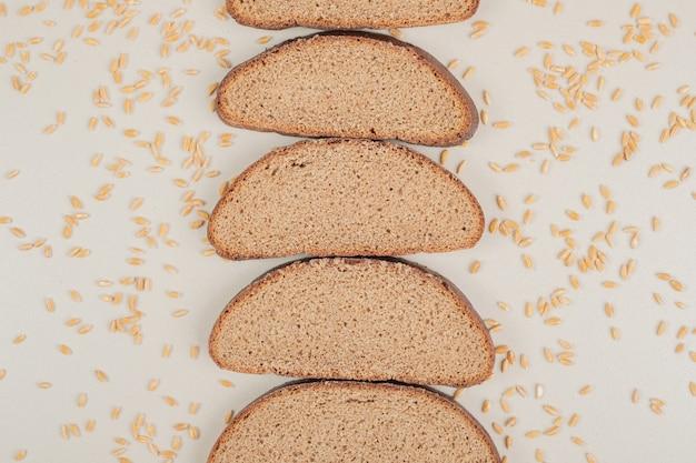 Pane integrale fresco affettato con chicchi di avena sulla superficie bianca