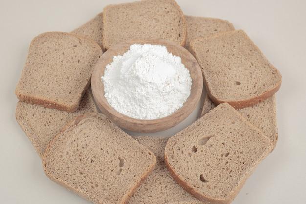 Pane integrale fresco affettato con ciotola di legno di farina sulla superficie bianca