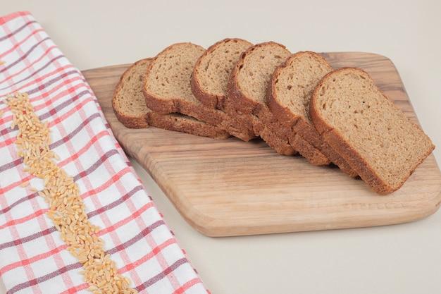 Pane integrale fresco affettato sulla tavola di legno