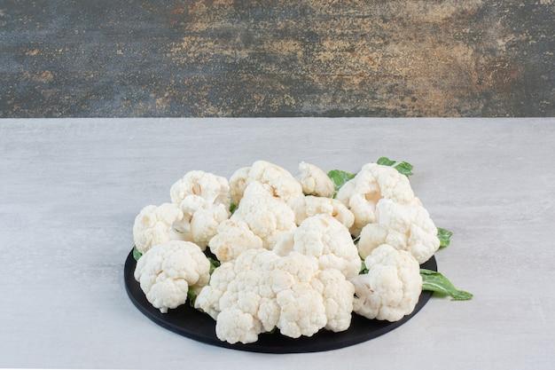 Sliced fresh cauliflower with leaves on black board. high quality photo