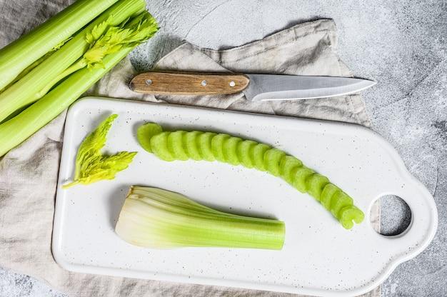 Sliced fresh celery stalk on cutting white board.