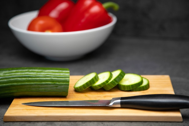 Sliced fresh cucumber on a cutting board with a knife and a ceramic plate of vegetables.
