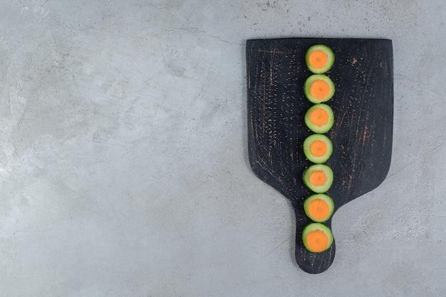 Нарезанные свежие огурцы с нарезанной морковью на темной доске. фото высокого качества