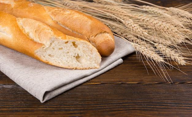 スライスした新鮮なフランスパンをカットして、素朴な木製のテーブルに小麦の新鮮な熟した穂と一緒にテクスチャーを表示します。クローズアップビュー