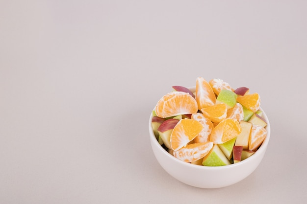 Sliced fresh fruits in white bowl.