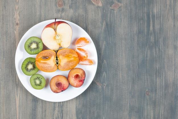 Sliced fresh fruits on white plate