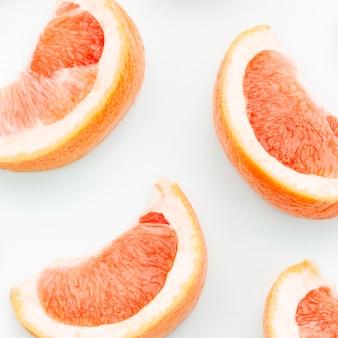 Sliced fresh grapefruit on white background