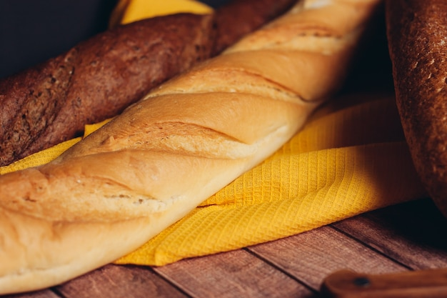 木製のまな板のキッチンで新鮮なパンをスライスしました。