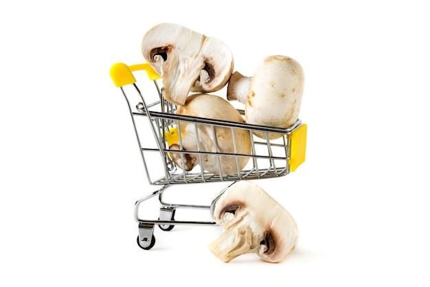 孤立した背景の小さな買い物かごに新鮮なキノコをスライス