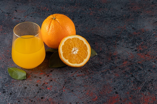 Sliced fresh orange fruit with leaves and a glass pitcher of juice placed on stone table.