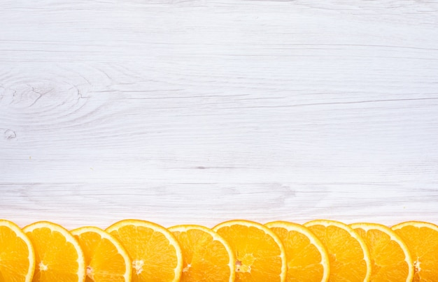 Sliced fresh orange fruits top view with copy space on wooden surface