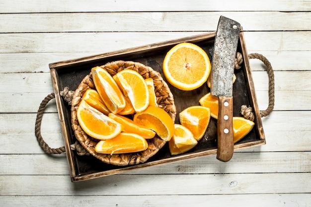 木製のトレイに新鮮なオレンジをスライスしました。白い木製のテーブルの上。