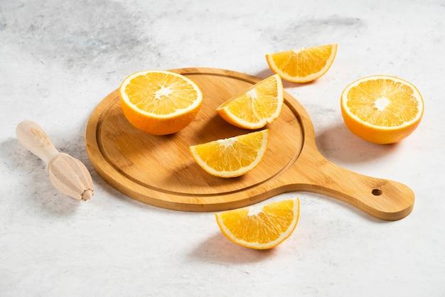 Arance fresche a fette con alesatore in legno su marmo.