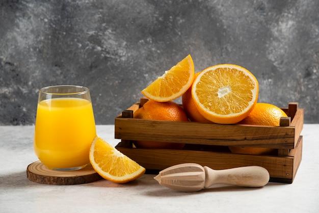 Нарезанные свежие апельсины с деревянной разверткой на мраморе.