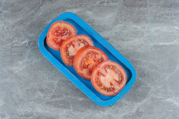青い木の板に新鮮な有機トマトをスライスしました。