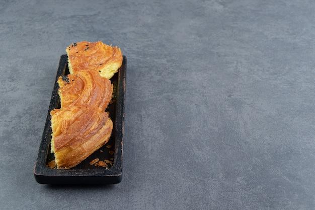 검은 접시에 얇게 썬 신선한 생 과자입니다.
