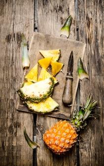 木製のテーブルのまな板の上でナイフで新鮮なパイナップルをスライスしました。上面図