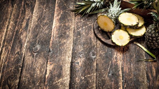 Sliced fresh pineapple on wooden table.