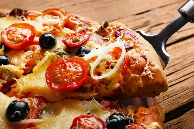 木製のテーブルのクローズアップでスライスした新鮮なピザ
