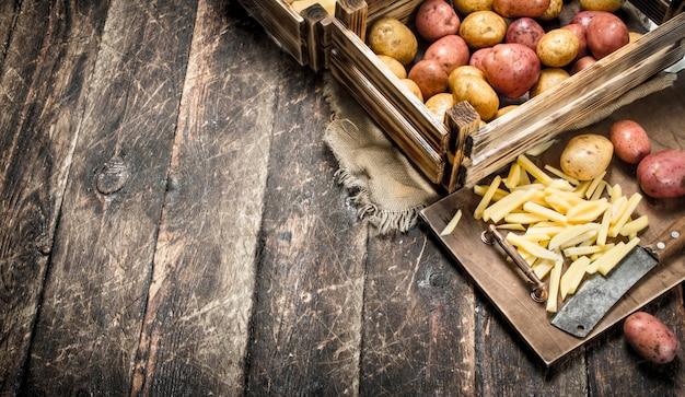 古いハチェットで新鮮なジャガイモをスライスしました。木製のテーブルの上。
