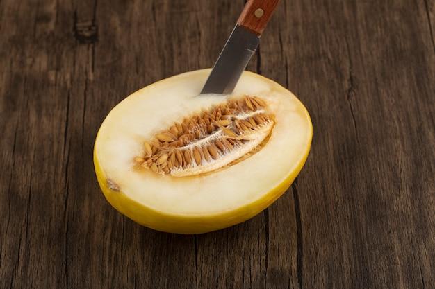 Fette di frutta fresca matura dolce melone melata con un coltello su un tavolo di legno.