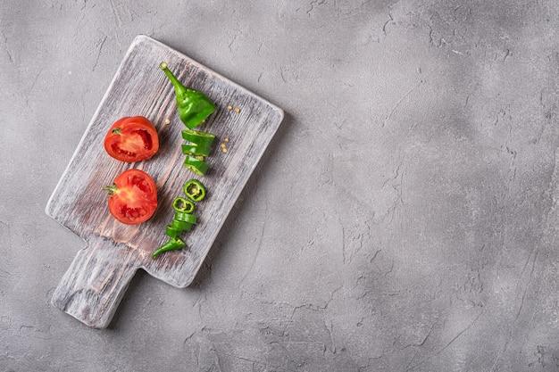古い木製のまな板に唐辛子とスライスした新鮮な完熟トマト