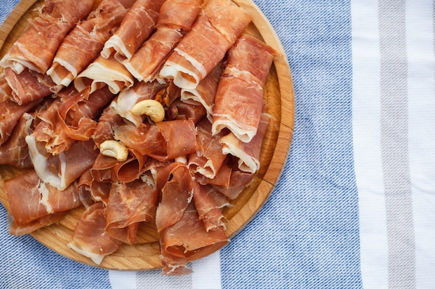 Sliced fresh rolls of jamon on wooden tray at picnic blanket. summer weekends