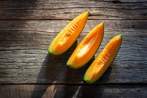 木製の板にスライスした新鮮な甘いメロン。オレンジ色の質感。上面図 。